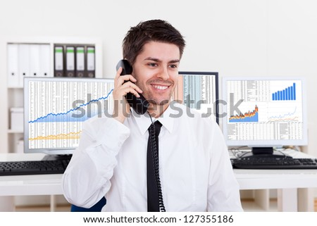 Enthusiastic young male stock broker in a bull market holding a telephone