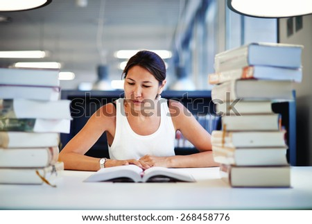 Entrained female student learning at the desk with a huge pile of study books in university library, young asian college student reading interesting textbook looking so absorbed with the content - stock photo