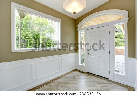 Entrance hallway with tile floor and beige wall with white trim. White door with arch and windows - stock photo