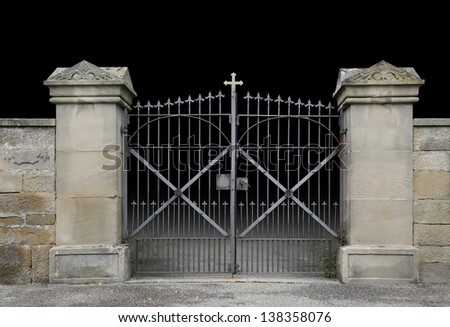 entrance of a graveyard with a closed wrought-iron gate in dark gradient back - stock photo
