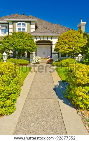 Entrance of a house with nice outdoor landscape over blue sky - stock photo