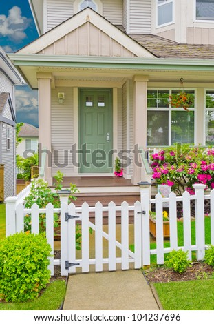 Entrance of a house with the country style wooden fence in front of - stock photo