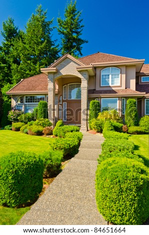 Entrance of a large luxury house with beautiful outdoor landscape over a blue sky and big trees. - stock photo