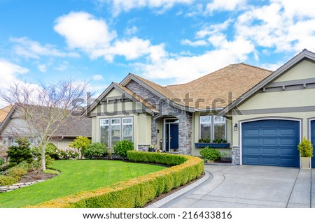 Entrance of a luxury house with beautiful landscaping on a bright, sunny day. Home exterior design. - stock photo
