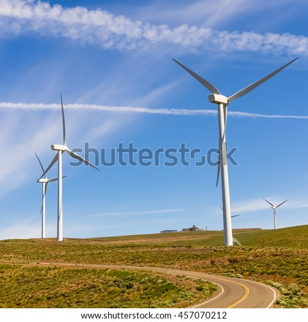 Entrance of a wind farm with the asphalt road leads to horizontal and row of wind turbines again blue cloud sky in background. Clean, sustainable, renewable energy concept. Alternative energy source.