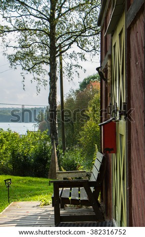 Entrance of a wooden rural house, with wooden green door, surrounded by green garden. Wooden porch with wooden bench and red postbox. View from hill to lake water. - stock photo