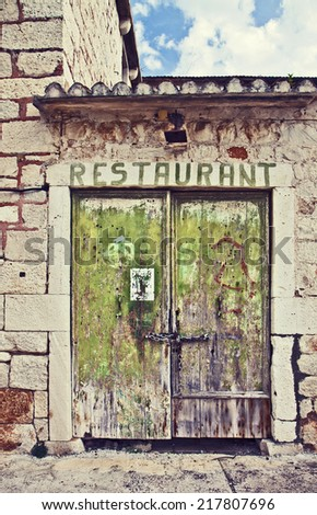 Entrance of an old and abandoned building locked with chain. Instagram-like retro effect added. - stock photo