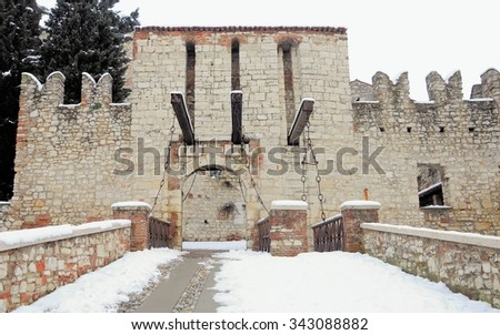 Entrance of medieval building with a drawbridge and snow. - stock photo