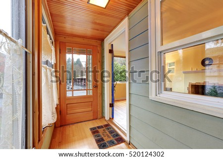Entrance porch interior with wood paneling, window curtains and doormat. Northwest, USA