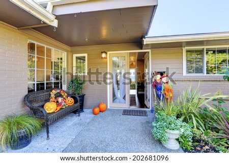 Entrance porch with wicker bench, flower pots and pumpkin decoration - stock photo