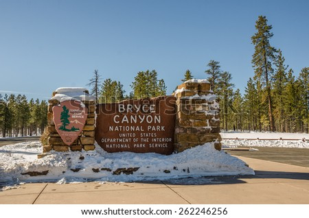 Entrance sign for Bryce Canyon National Park in Utah on a beautiful winter day with a bit of snow..A fir forest is in the background. The sign is made from the limestone that you find in the park. - stock photo