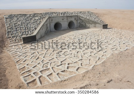 Entrance to a large underground drainage pipe dyke - stock photo