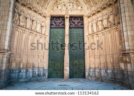Entrance to beautiful cathedral in Spain. Famous old church in Toledo. Two green doors and walls with sculptures of saints. Religious scene above doorway. Popular tourist attraction in Europe. - stock photo