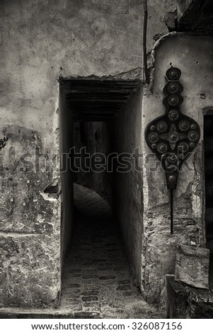 Entrance to dark alley in Fes medina, black and white image. - stock photo