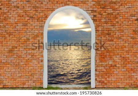 Entrance to ocean of door on wall brick twilight sky - stock photo