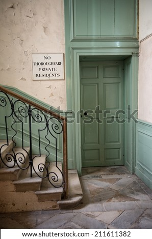 Entrance to private quarters in a historical house or castle that is open to the public with a staircase with ornate wrought iron railing, closed green door and notice denying access - stock photo