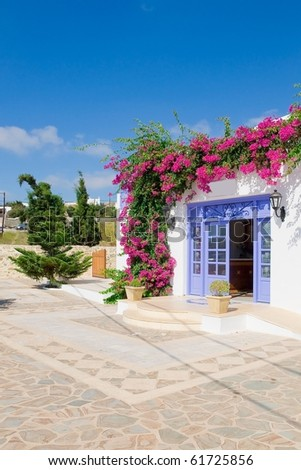 Entrance to the house decorated with flowers and yard with trees - typical in Greece . - stock photo