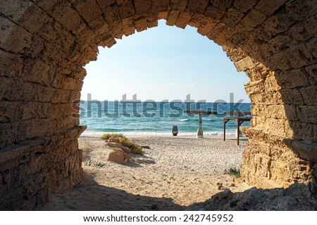 Entrance to the sand beach through the arch of aqueduct near Caesarea, Israekl                                - stock photo