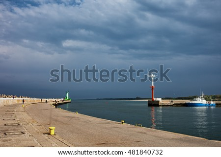 Entrance to the Wladyslawowo port at Baltic Sea in Poland, view from pier, stormy sky