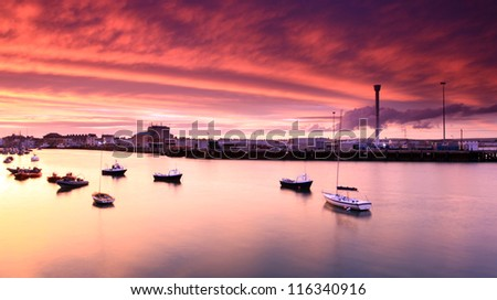 Entrance to weymouth harbour at dusk in southern england - stock photo