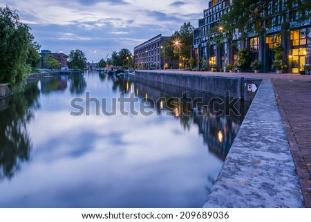 Entrepotdok canal, Amsterdam 5. Shortly after the sun had set on Nieuwevaart canal, I moved to another location nearby- a more sheltered waterway where the reflections were beautiful. - stock photo