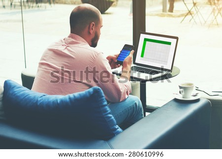 Entrepreneur analyzing financial information as graphics and charts on his notebook and smart phone, young business busy working on laptop computer sitting at sofa of modern coffee shop or hotel hall - stock photo