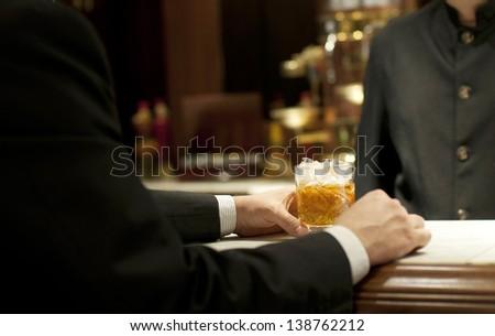 Entrepreneur drinking whiskey at the bar - stock photo