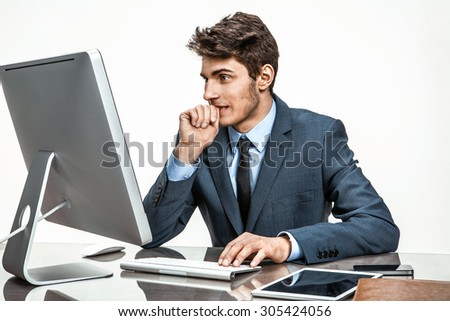 Entrepreneur looking at computer screen with horror / modern businessman at the workplace working with computer, depression and crisis concept