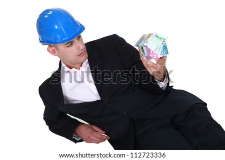 Entrepreneur lying on the floor with a house-shaped box in hand - stock photo