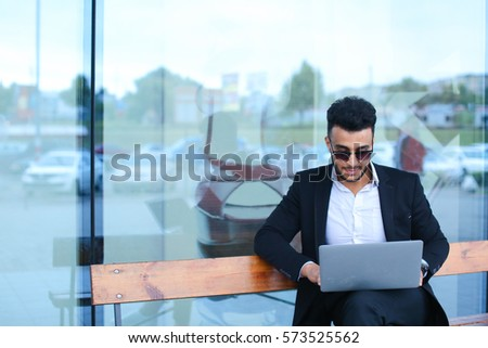 Entrepreneur uses laptop wearing sunglasses. Young handsome businessman arab muslims in business center wearing dressed in black elegant suit on building background.