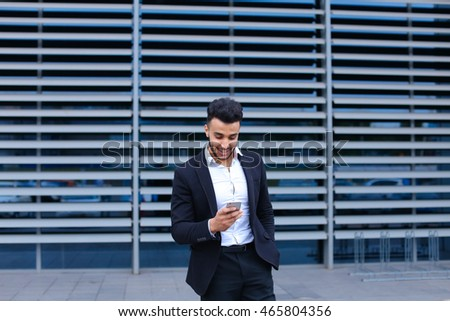 Entrepreneur uses phone mobile smart looking at the camera. Young handsome businessman arab muslims in business center wearing dressed in black elegant suit on building background.