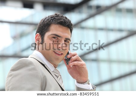 Entrepreneur using a cellphone outside a mirrored building - stock photo