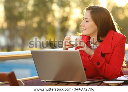 Entrepreneur with a laptop relaxing in a coffee shop and looking forward - stock photo