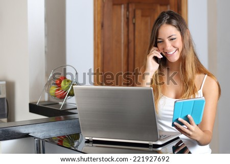 Entrepreneur woman multi tasking working with a laptop tablet and phone in the kitchen at home - stock photo