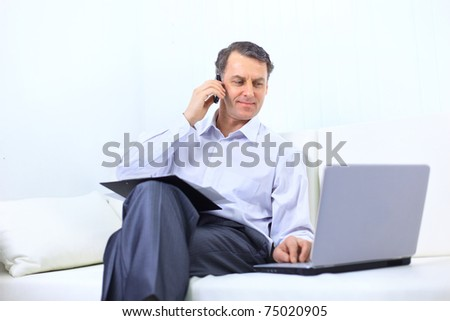 entrepreneur working from home looking very relaxed in his sofa browsing the web in his laptop computer - stock photo
