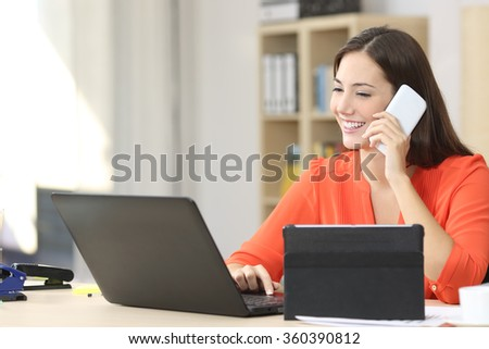 Entrepreneur working on line with multiple devices in a desk in a little office or home - stock photo