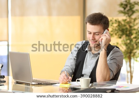Entrepreneur working on the phone and writing notes sitting in a desk at office - stock photo