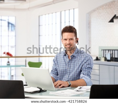 Entrepreneur working with laptop at office desk, looking at camera. - stock photo