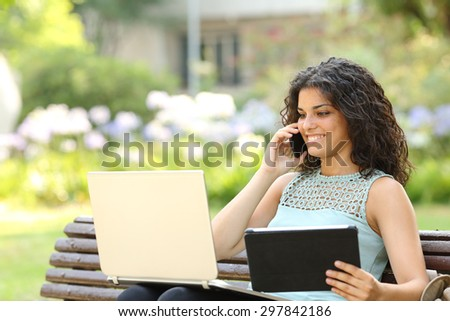 Entrepreneur working with multiple devices sitting in a bench in a park - stock photo