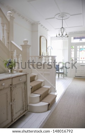Entry hall with stairway and front door - stock photo
