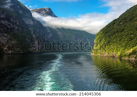 Entry into the beautiful Geiranger Fiord, Norway with a low lying cloud bank - stock photo