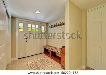 Entryway in light tones with mosaic tile floor, bench seat, built-in wardrobe and hangers on the wall. Northwest, USA