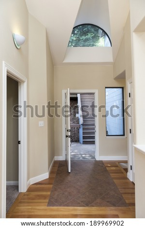 Entryway with wooden floor, high ceiling, round window and adjacent room - stock photo