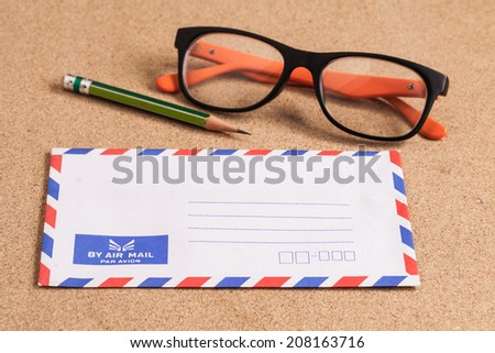 envelope and pencil on wooden background. - stock photo