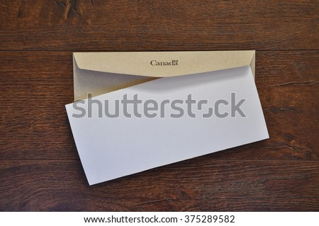 Envelope with Canada written in it and white folded paper - stock photo