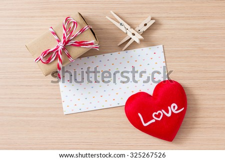 Envelope with red heart, peg, gift box valentine day on wooden table background - stock photo