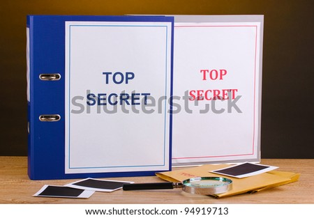 Envelopes and folders with top secret stamp and magnifying glass with photo papers on wooden table on brown background - stock photo