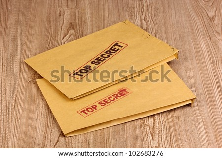Envelopes with top secret stamp on wooden background - stock photo