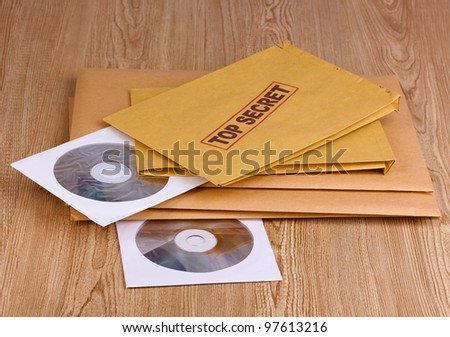 Envelopes with top secret stamp with CD disks on wooden background - stock photo