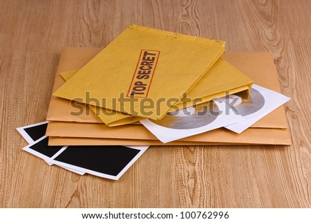 Envelopes with top secret stamp with photo papers and CD disks on wooden background - stock photo